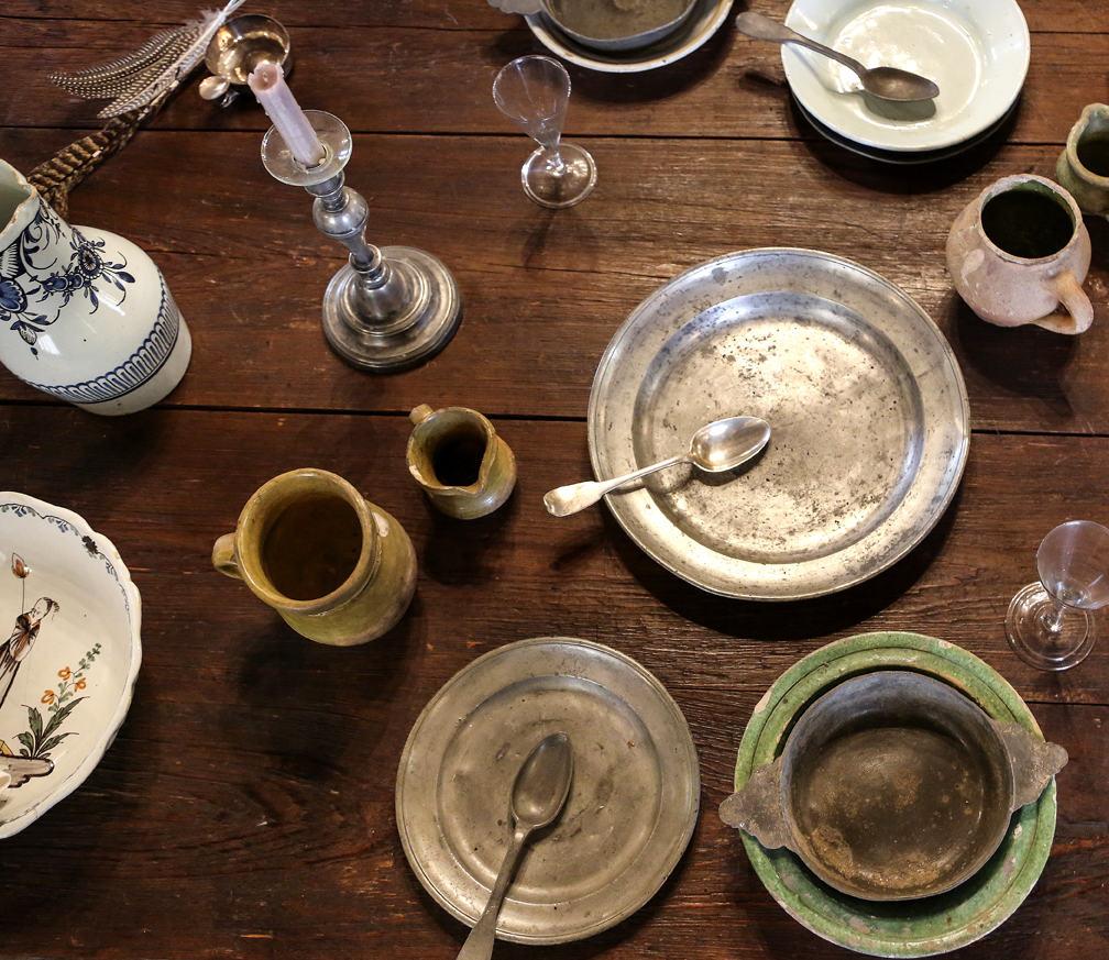 An assortment of pitchers, bowls and other artifacts unearthed during archaeological excavations in Louisiana is displayed on a trestle table in the LaCour House's smaller room.