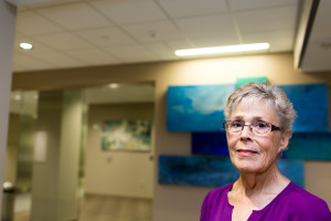 "Nora Taylor, two-time cancer survivor, stands in front of Robert Rector's ""Waters of the World."" The artwork in the facility is meant to be directional, guiding patients from one corridor to the next."