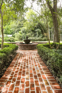 A brick path and fountain lead into the backyard, which was dense with camellias and azaleas before being thinned to make room for family-friendly features like a treehouse and zip line. Richard Netzberger of Groundworks was responsible for the new landscape design.