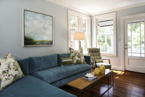 """The master suite has its own adjacent sitting area that overlooks the backyard and pool. The painting over the sofa is by local artist Lynn Washauer. """"At first I was a little leery of having a smaller bedroom with a separate sitting area,"""" says Mike. """"Now I really appreciate having a smaller, cozy room for sleeping with a more lively and open room for watching TV and relaxing."""""""